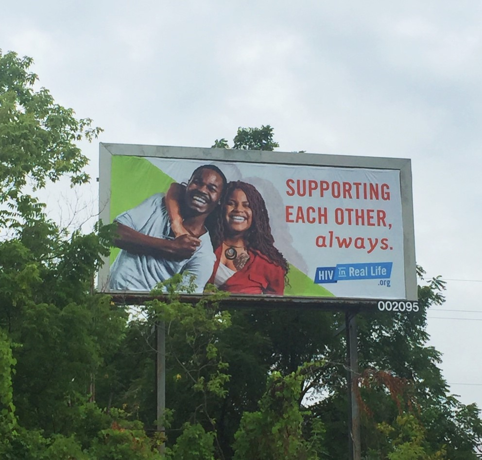 A photograph of a billboard along the road about the HIV campaign.